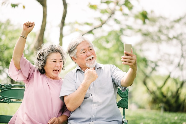 Senior asian couple laughing with smartphone Premium Photo