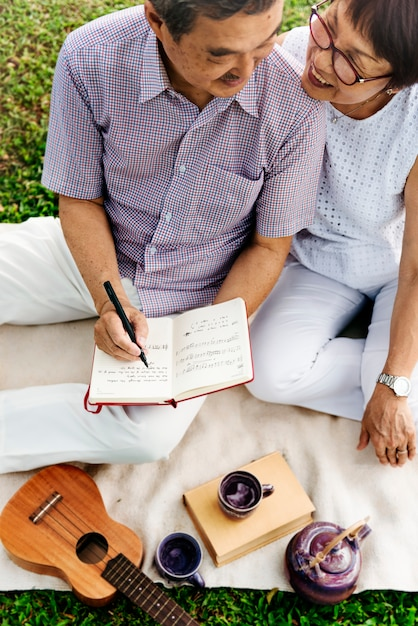 Senior asian couple picnic writing music ukulele concept Premium Photo