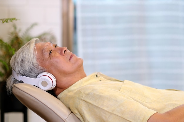 Senior asian man listening headphones whlie laying on sofa in home living room with happiness Premium Photo