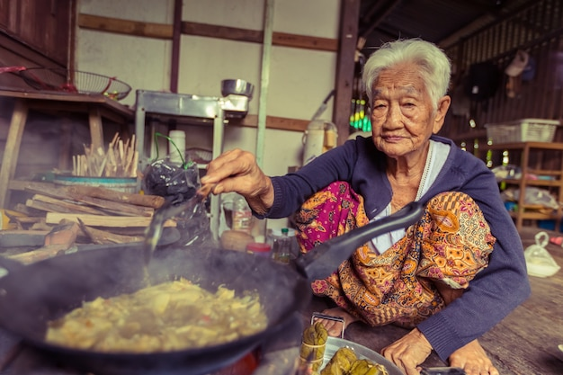 Senior asian woman chef cook in the kitchen, traditional in thailand Premium Photo