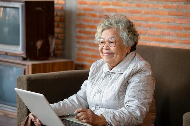 ソファに座っているアジアのシニアの女性は、ソーシャルネットワークを使用して自宅で自由な時間を過ごし、友人や子供たちとチャットして楽しんでいます。 Premium写真