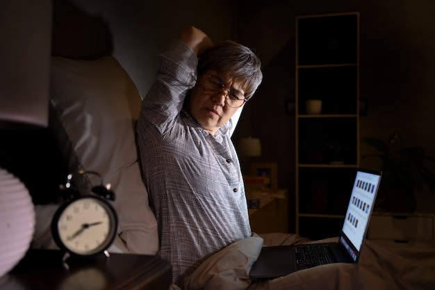 Senior asian woman with sore and muscle pain from laptop use in bed Premium Photo