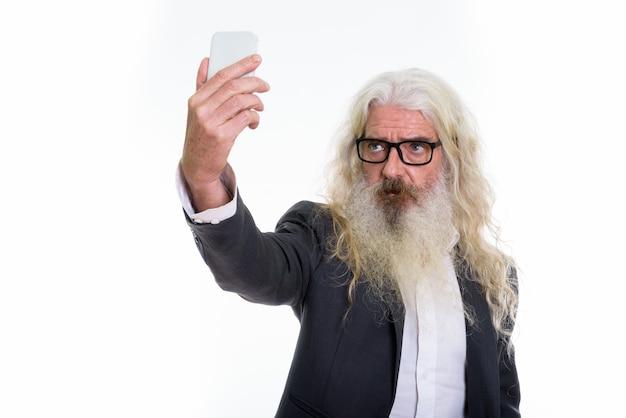 自撮り写真を撮るシニアひげを生やしたビジネスマン Premium写真