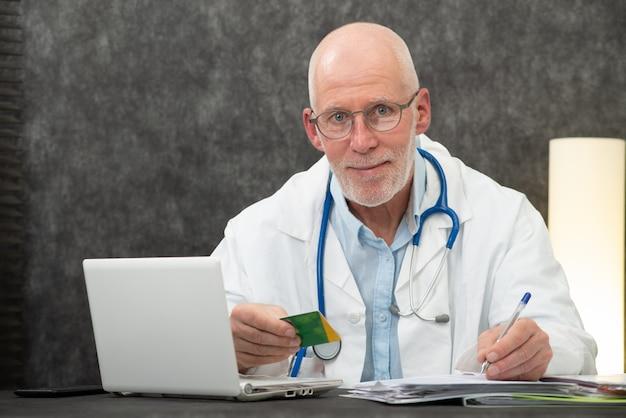 Senior bearded doctor with health insurance card Premium Photo