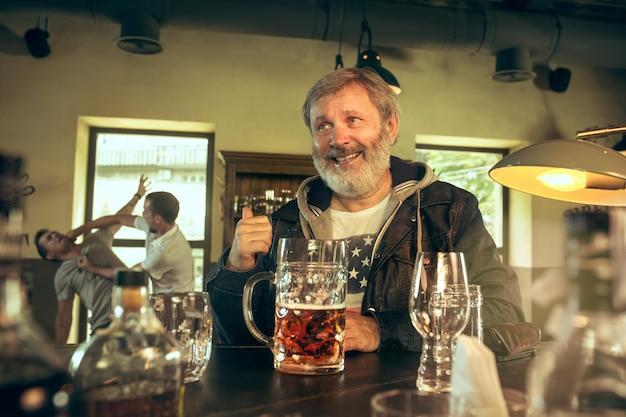 Uomo barbuto anziano che beve alcolici in un pub e guarda un programma sportivo in tv. gustare la birra. uomo con boccale di birra seduto a tavola. appassionato di calcio o di sport. Foto Gratuite