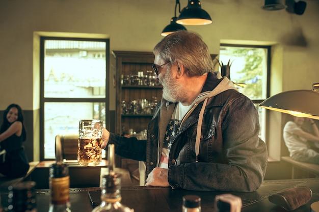 Uomo barbuto anziano che beve alcolici in un pub e guarda un programma sportivo in tv. gustando il mio brulicare e la mia birra preferiti. uomo con boccale di birra seduto a tavola. appassionato di calcio o di sport. concetto di emozioni umane Foto Gratuite