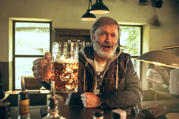 Uomo barbuto anziano che beve alcolici in un pub e guarda un programma sportivo in tv. gustando il mio brulicare e la mia birra preferiti. uomo con boccale di birra seduto a tavola. Foto Gratuite