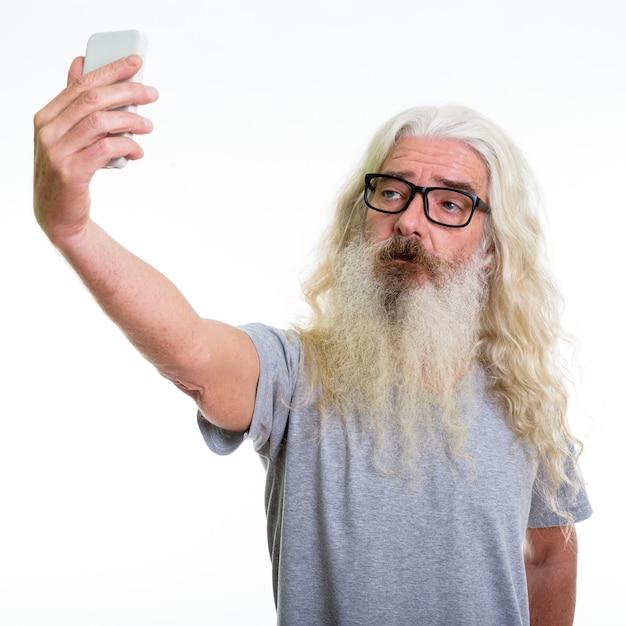 携帯電話で自分撮り写真を撮るシニアひげを生やした男 Premium写真