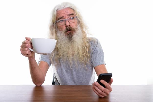 モバイルを保持しながら考えるシニアひげを生やした男 Premium写真