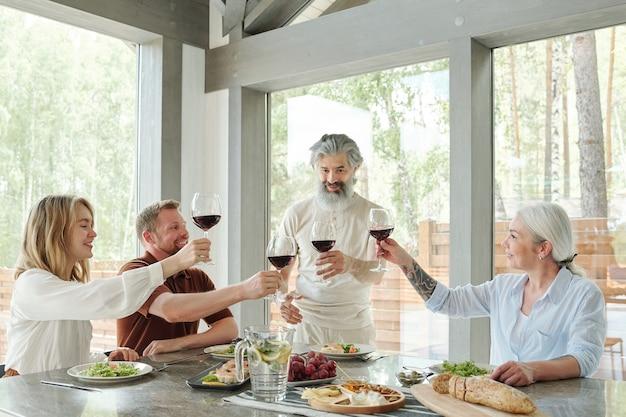 Старший бородатый мужчина с бокалом красного вина, пьющий тост с членами семьи во время ужина Premium Фотографии