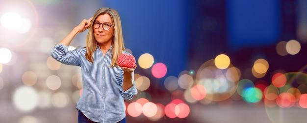 Senior beautiful woman with a brain model Premium Photo