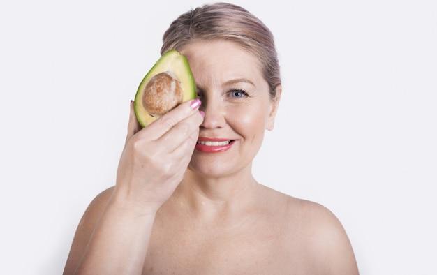 アボカドの笑顔で彼女の顔を覆っている裸の肩を持つ年配のブロンドの女性 Premium写真