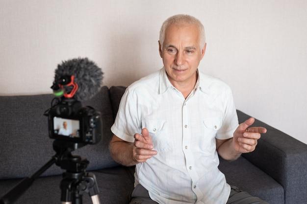 Старший бизнесмен, снимающий онлайн-курс обучения дома с помощью видеокамеры Premium Фотографии