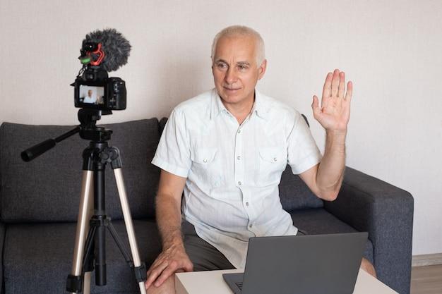 Старший бизнесмен делает дома видео для блога с помощью видеокамеры Premium Фотографии