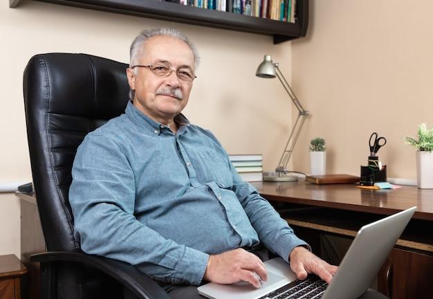 수석 사업가 집에서 작동합니다. 안경을 쓴 노인이 노트북을 사용하여 원격으로 일하고 있습니다. Coronovirus 개념 중 원격 작업 프리미엄 사진