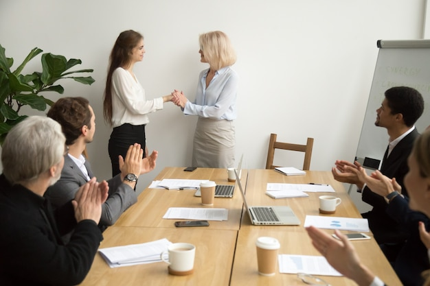 Senior businesswoman boss promoting thanking female employee while team applauding Free Photo