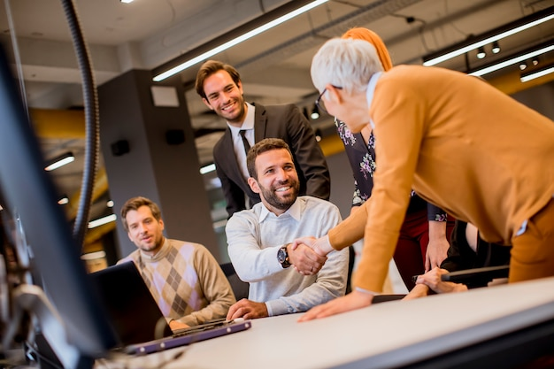 Senior businesswoman working together with young business people in modern office Premium Photo