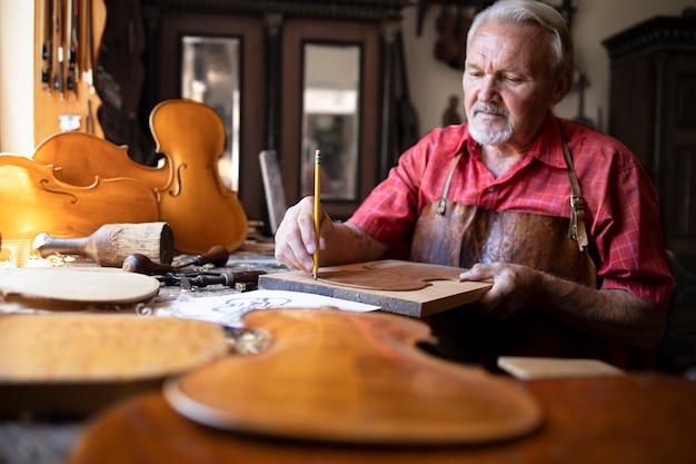Старший плотник делает скрипку музыкальный инструмент в своей старинной столярной мастерской. Бесплатные Фотографии