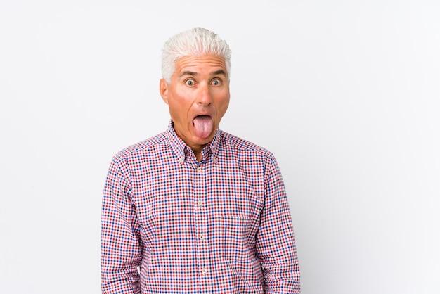 シニア白人男性は、面白くてフレンドリーな舌を突き出して孤立しました。 Premium写真