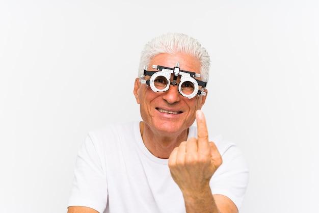 Старший кавказский мужчина в пробной оправе оптометриста, указывая пальцем на вас, как будто приглашая подойти ближе. Premium Фотографии