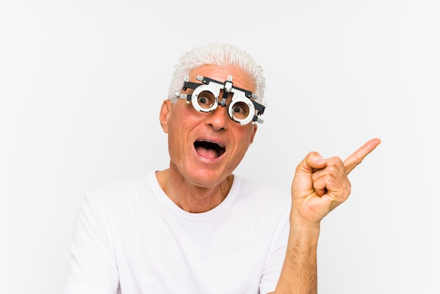 Senior caucasian man wearing a optometrist trial frame smiling cheerfully pointing with forefinger away. Premium Photo
