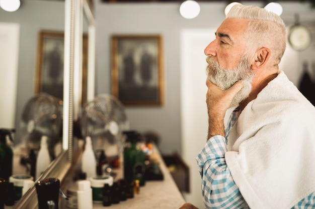 Senior client estimating work of barber in mirror Free Photo