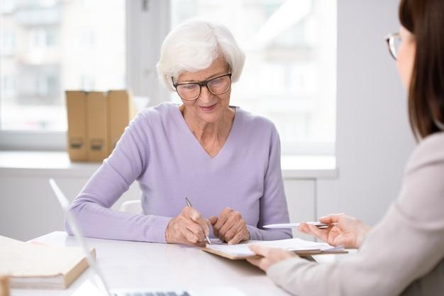 Старший клиент ставит свою подпись в договоре страхования после обсуждения его условий с агентом на встрече Premium Фотографии