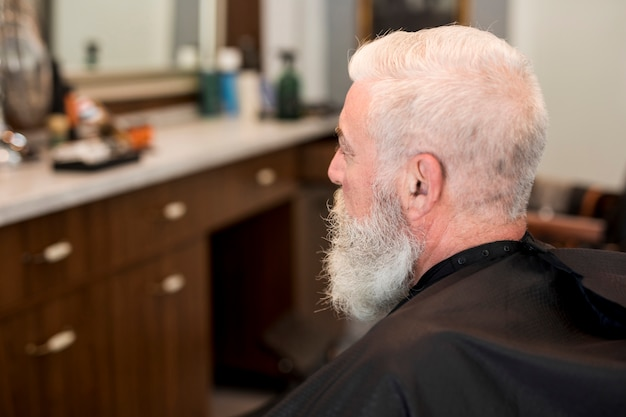 Senior client with cape in barbershop Free Photo