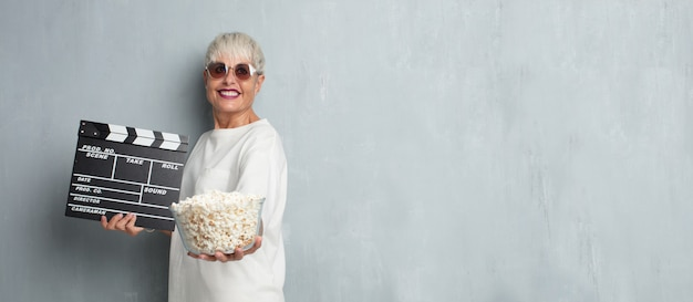 Senior cool woman with pop corns against grunge cement wall. cin Premium Photo