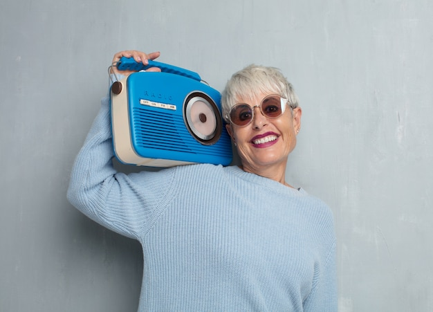 Senior cool woman with a vintage radio, listening music against Premium Photo