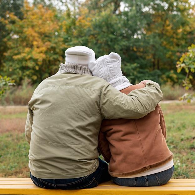 Senior couple on bench hugging Free Photo