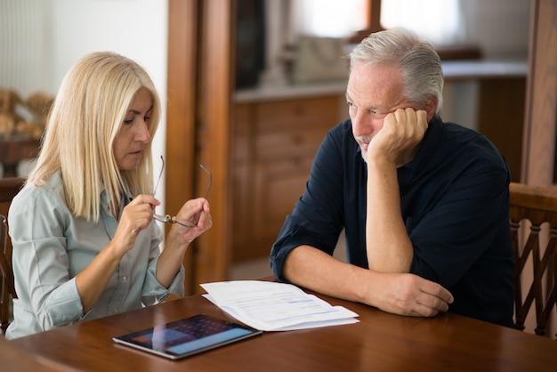 Senior couple calculating their living expenses together Premium Photo