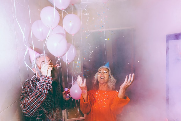 Senior couple celebrating the couple together in the smoky room decorated with pink balloons Free Photo