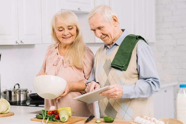Senior couple cooking in kitchen Free Photo