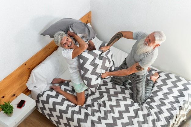 Senior couple doing pillow battle during morning time at home Premium Photo