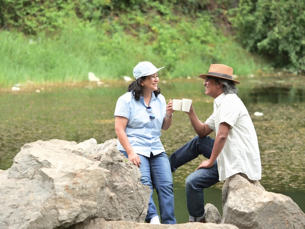 Senior couple enjoying camping trip, they drink coffee in the morning together. Premium Photo