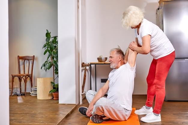 自宅で運動している年配のカップル、女性は床に座って、夫がストレッチするのを手伝います。幸福、健康的なライフスタイルの概念 Premium写真
