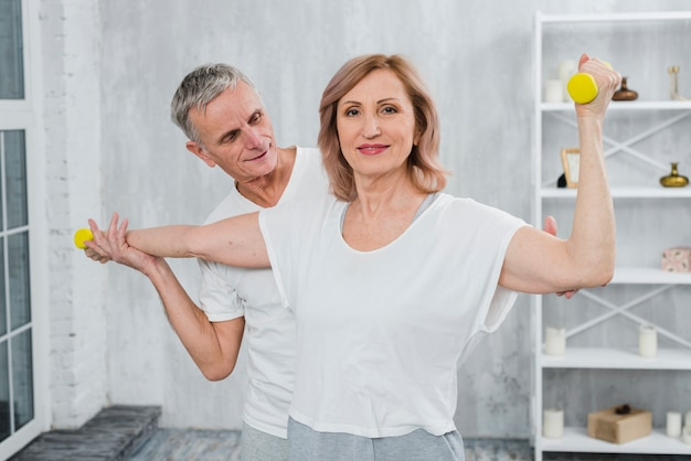 Senior couple exercising together at home with dumbbells Free Photo