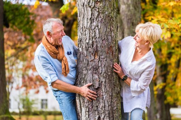 Senior couple flirting playing around tree in park Premium Photo
