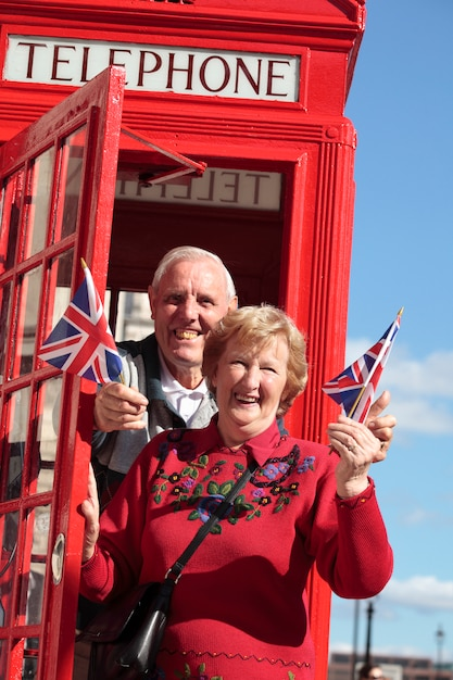 Senior couple in front of red telephone box Free Photo