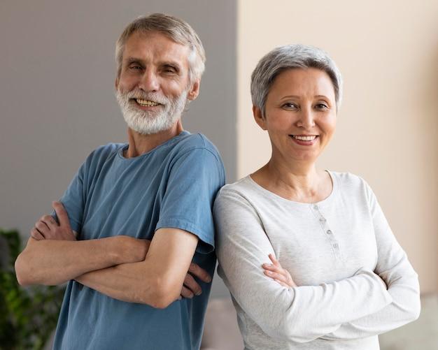 Старшая пара счастлива тренироваться вместе на дому Premium Фотографии
