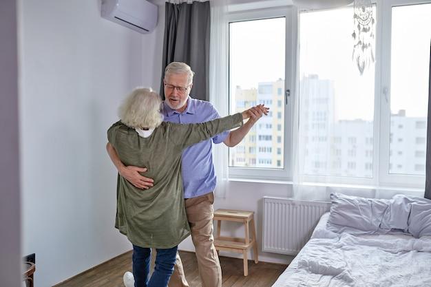 年配のカップルは家で踊るのが楽しいです、ロマンチックな成熟した白髪の男性と女性はエネルギッシュなアクティブを感じ、家族の退職の週末を楽しんで、一緒に休日を過ごします Premium写真