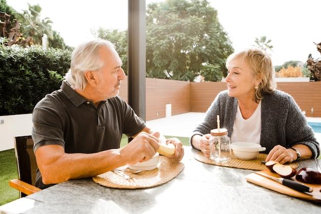 Senior couple having breakfast in garden Free Photo