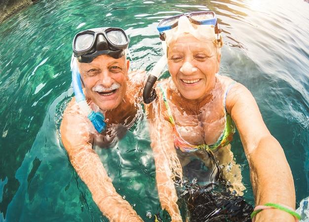 Senior couple having fun snorkeling at tropical beach Premium Photo