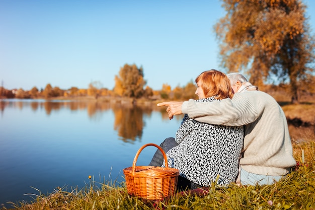 Senior couple having picnic by autumn lake happy man and woman hugging Premium Photo