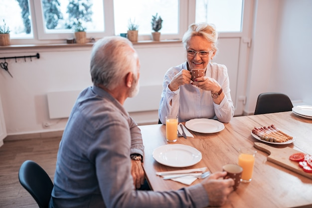 Senior couple having sitting at the table at home, eating breakfast. Premium Photo