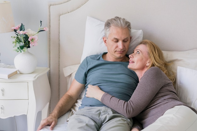 Senior couple hugging each other in bed Free Photo
