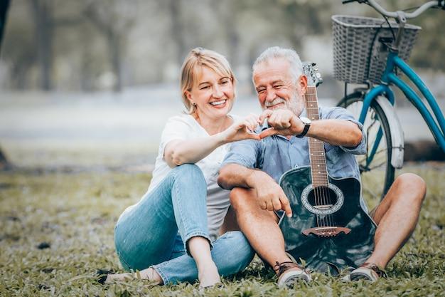 愛のショーのカップルは、公園で芝生に座ってハート型のアイコンを作った Premium写真