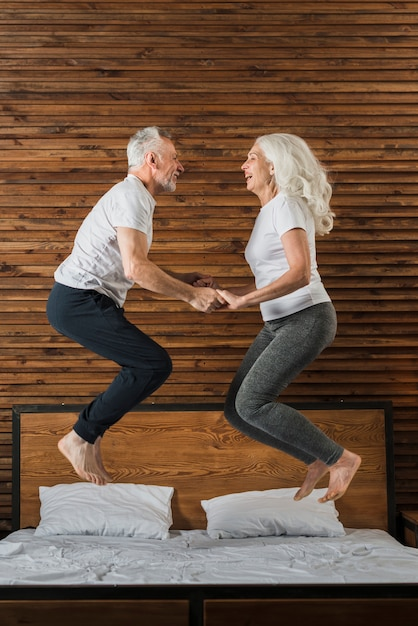 Senior couple jumping in bed Premium Photo