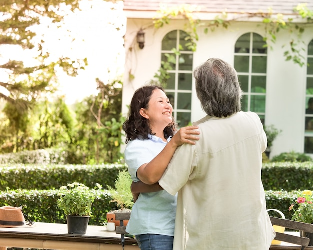 Senior couple laughing together in home garden. Premium Photo
